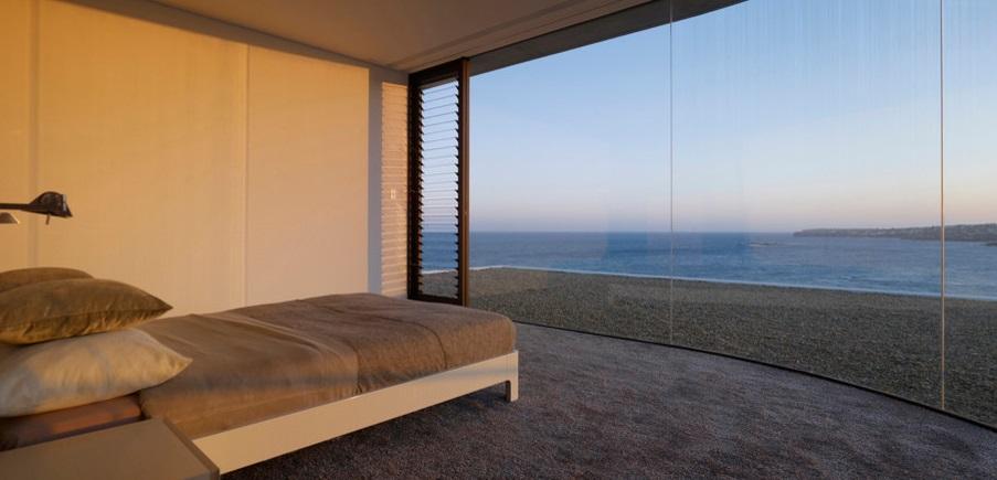 Спальня в серых тонах с видом на галечный пляж