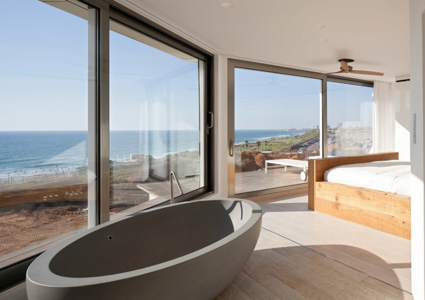 Современная ванная около кровати в спальни с незабываемым  видом