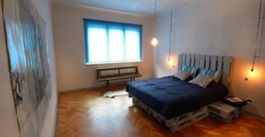 Красивая кровать из поддонов в интерьере спальной комнаты