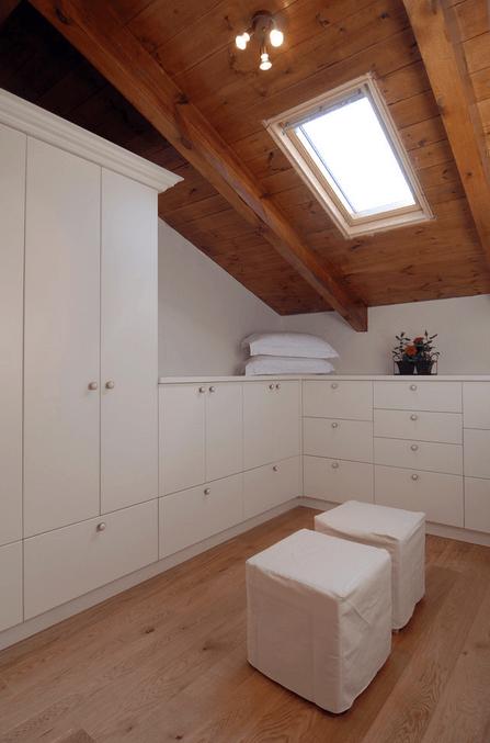 Белые шкафы в гардеробной на чердаке