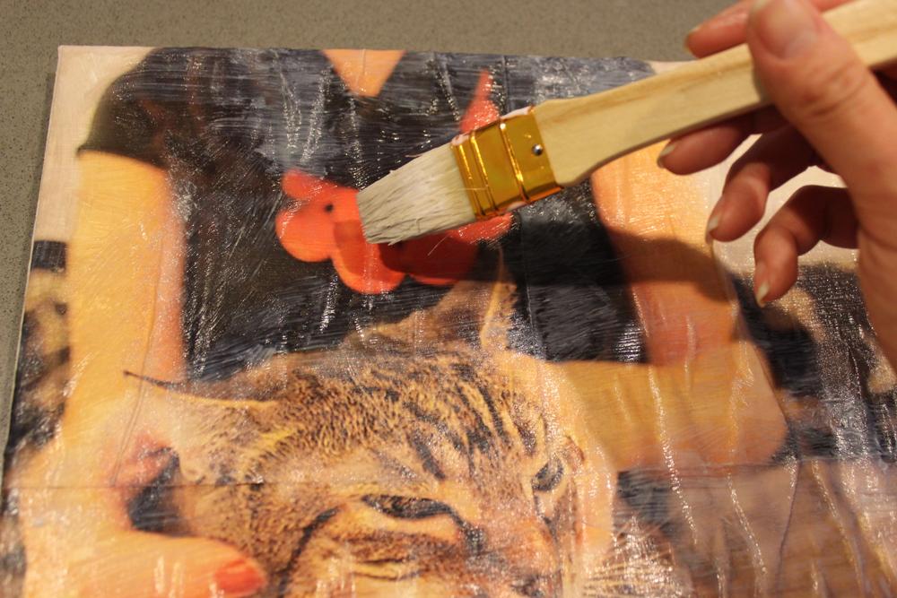 Нанесение клея на поверхность картины