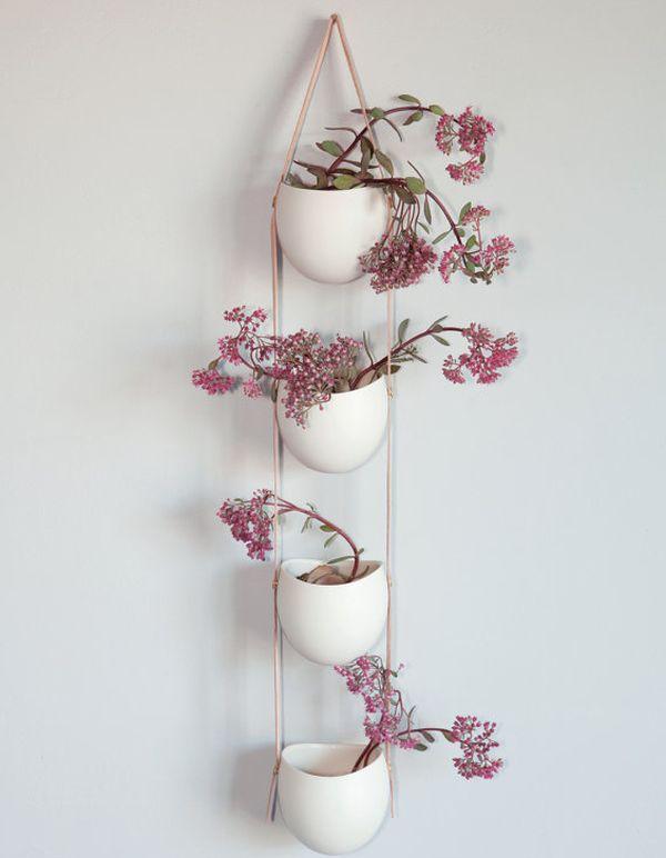 Красивые цветы в белых настенных горшках