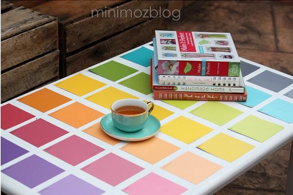 Чашка и книги на столике с яркими квадратиками переходящих цветов