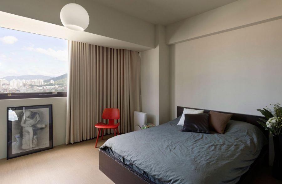 Яркий красный стул в минималистическом интерьере спальни