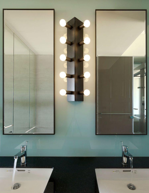Настенный светильник с гирляндой открытых лампочек в интерьере ванной комнаты