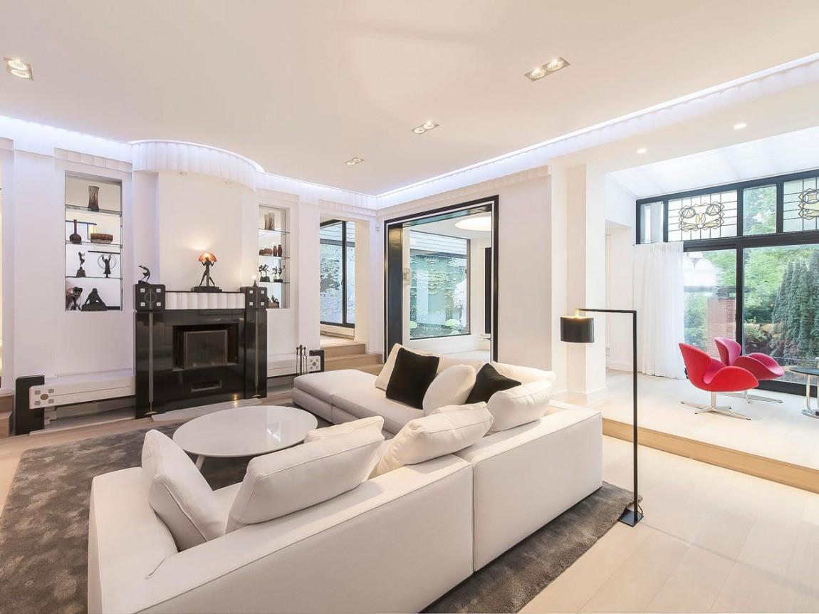 Белый угловой диван в гостиной апартаментов в стиле ар-деко
