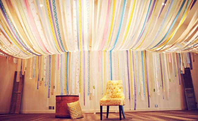 Декорирование потолка разноцветными текстильными ленттами в интерьере комнаты