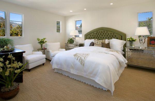 Нейтральная спальня с уютным зеленым изголовьем.