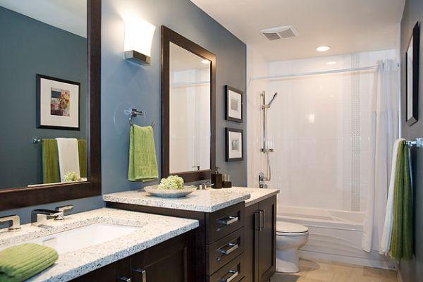 Несколько салатовых полотенец в современном дизайне ванной комнаты.