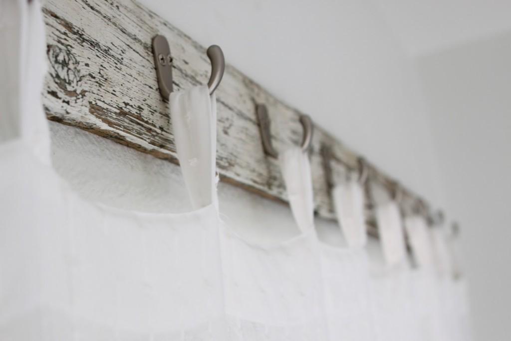 Деревянная вешалка с крючками в интерьере ванной