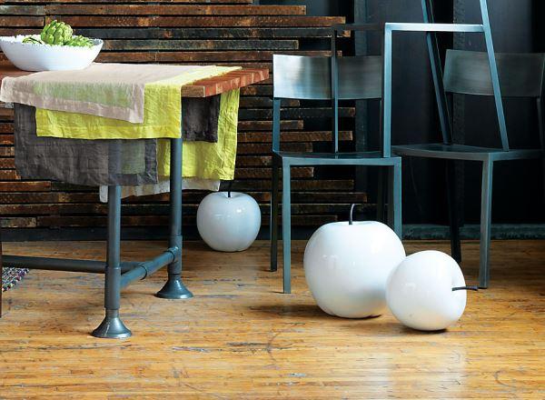 Декоративные яблоки в белом цвете на полу в интерьере