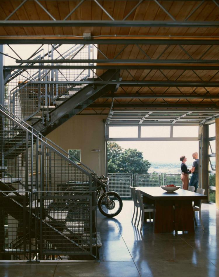 Металлическая лестница для подъема на второй уровень выполнена в промышленном стиле
