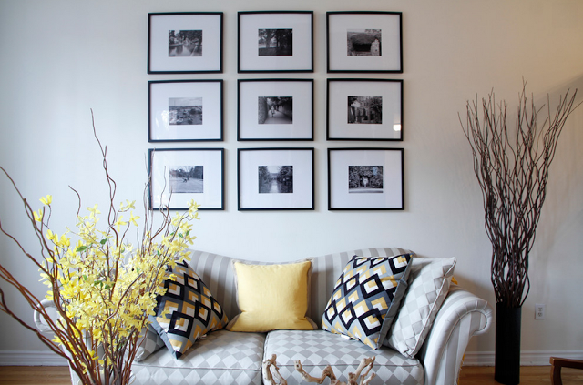 Черно-белые фото в рамках за диваном