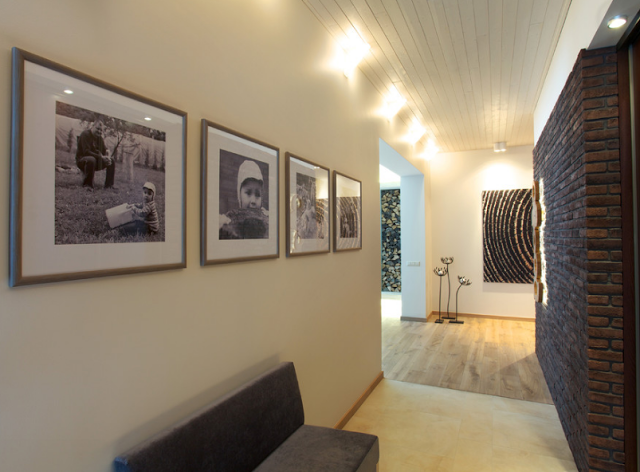 Черно-белые семейные фотографии на стене в коридоре