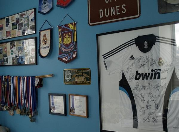 Спортивные футболки в рамках и медали на стене