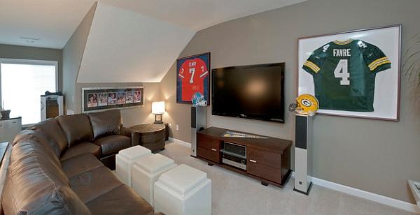 Спортивные футболки в рамках на стене в гостиной