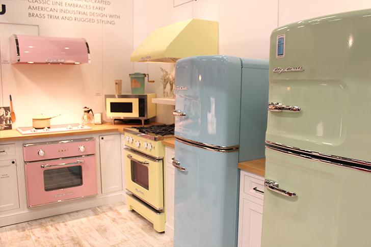 Нестандартная расцветка кухонной техники в стиле ретро: нежно-розовая  и светло-жёлтая плиты,  зелёный и голубой холодильники