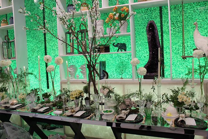 Яркий зелёный фон стены, отражающийся в зеркальной  поверхности стола