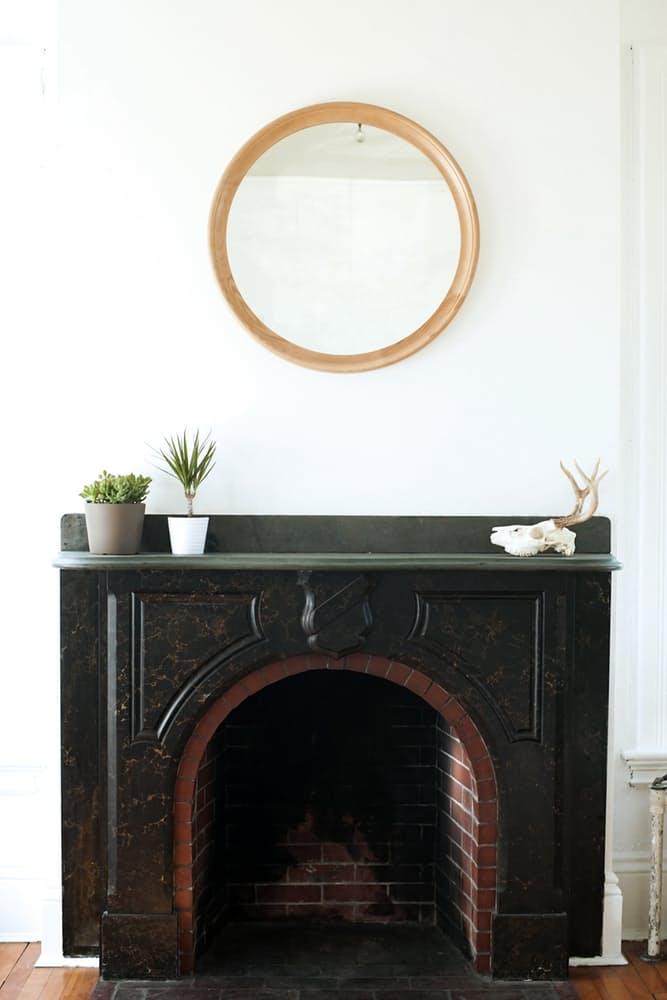 Интерьер дома в скандинавском стиле: круглое зеркало над камином