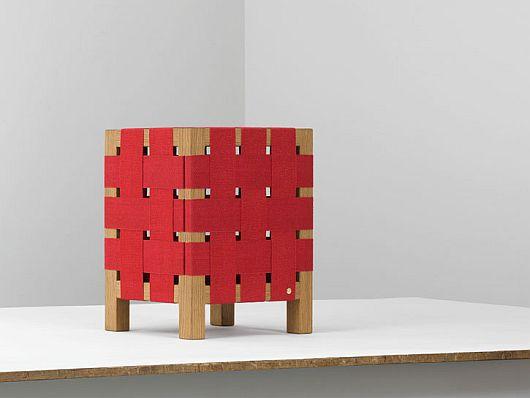 Кубический табурет, переплетённый красными кожаными ремнями