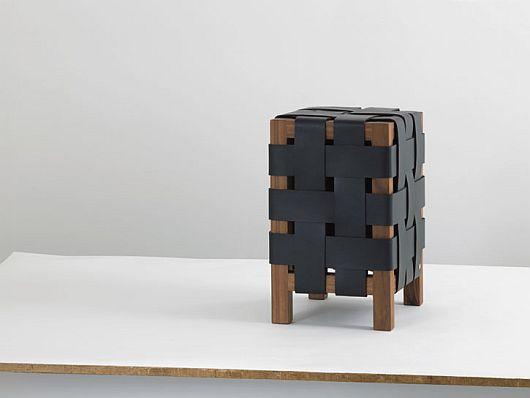 Табурет кубической формы, переплетённый ремнями чёрного цвета