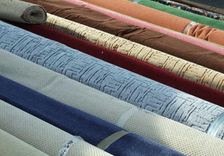 Рулоны разноцветных ковров разнообразной текстуры