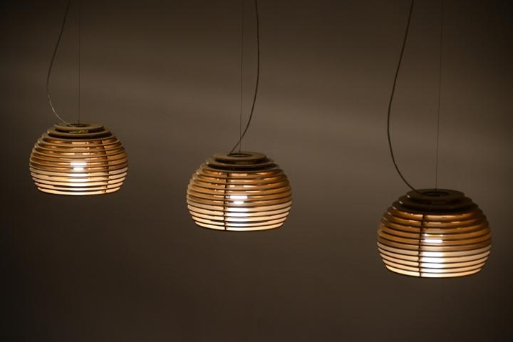 Три подвесные лампы из дерева в виде пчелиных ульев в интерьере ресторана