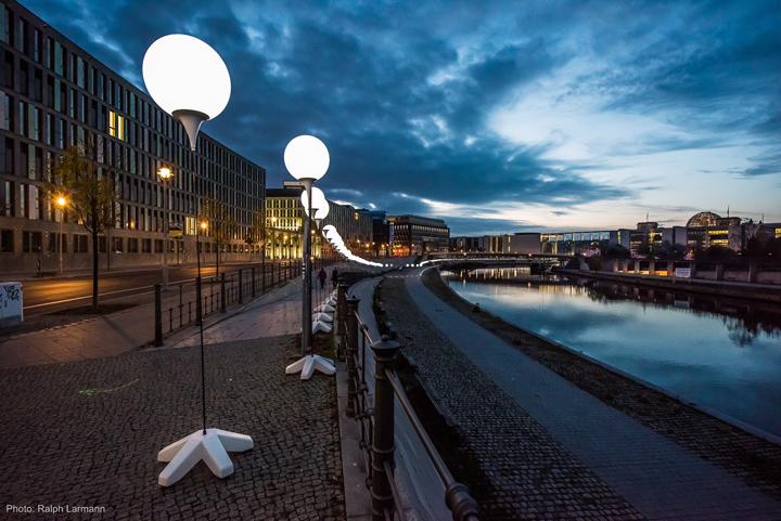 Осветительные установки около протикающей реки в Берлине