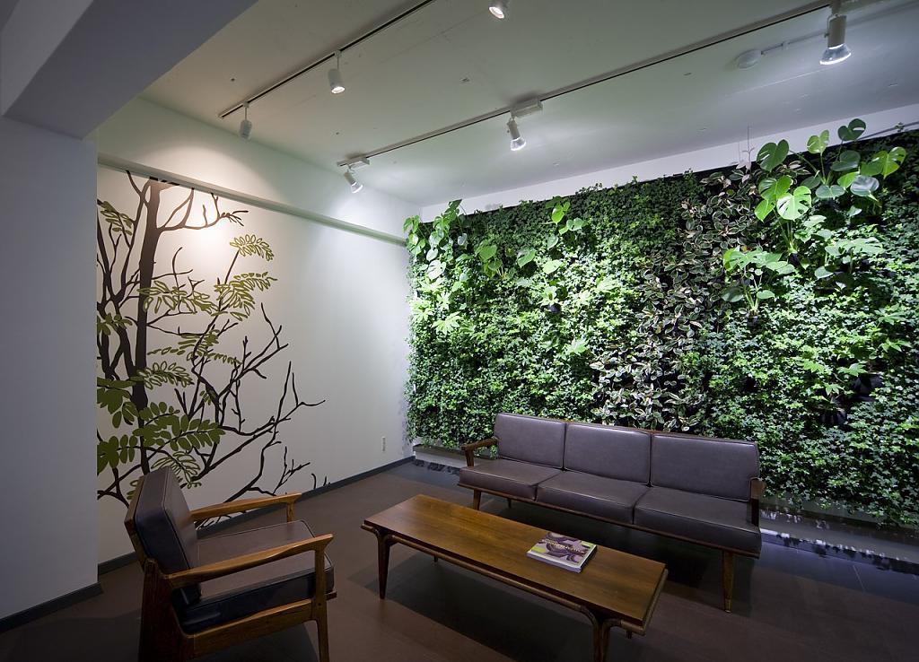 Кожаная скамья на фоне стены из растений