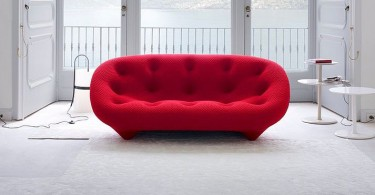 Красный дизайнерский диван в интерьере гостиной