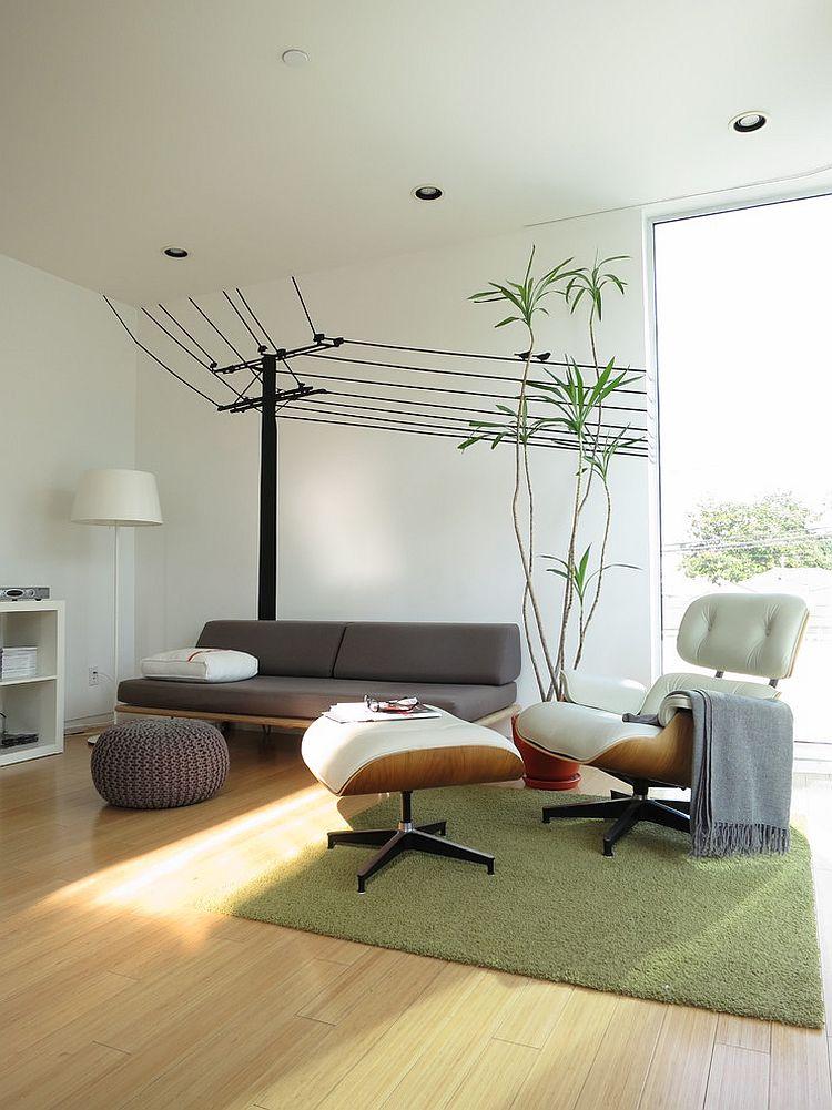 Серая тахта и роскошное кресло с подставкой для ног Eames Lounge Chair в интерьере комнаты