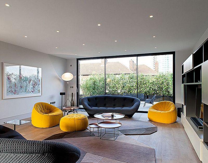Роскошный синий диван в интерьере гостиной на фоне ярких жёлтых кресел