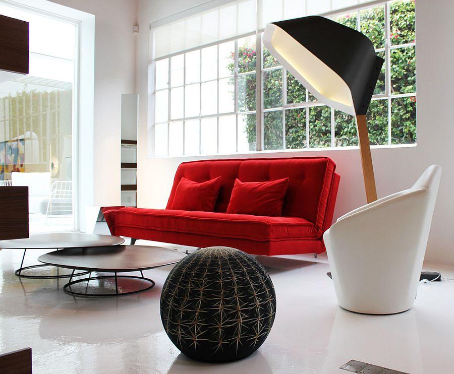 Яркий красный диван с подушками в светлом интерьере комнаты