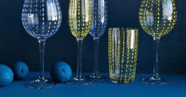 Бокалы из цветного стекла на синей скатерти стола