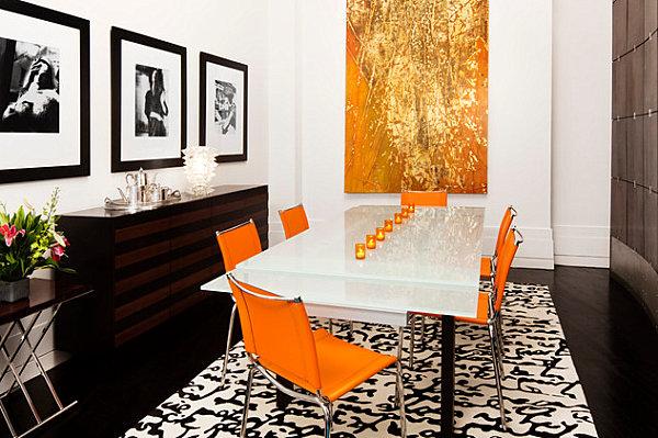 Оранжевые стулья и яркая оранжевая картина в столовой