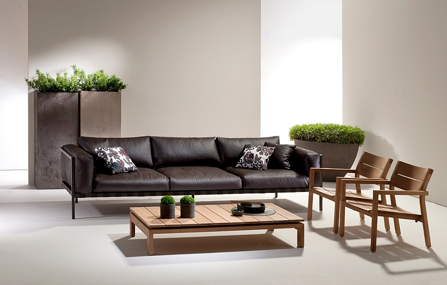 Длинный кожаный диван, деревянные кресла и стол в гостиной