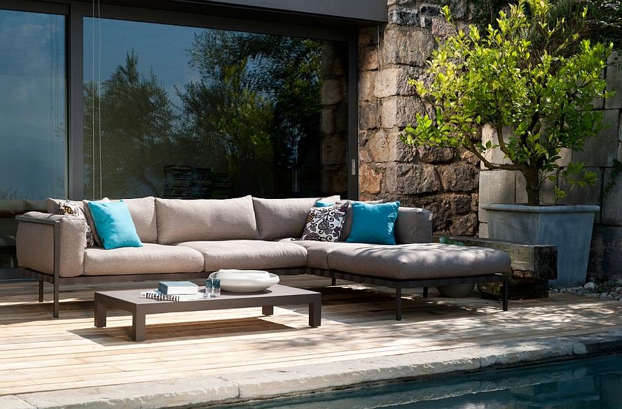 Угловой диван и деревянный стол на террасе
