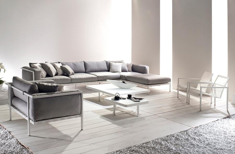 Мягкое кресло, диван, стулья и столы в интерьере светлой гостиной