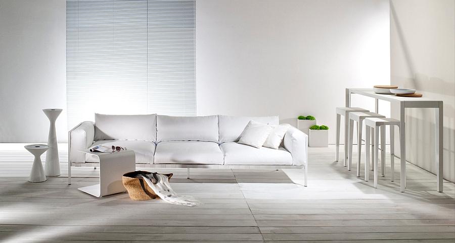 Белый диван, столы, табуретки и тумбы в гостиной