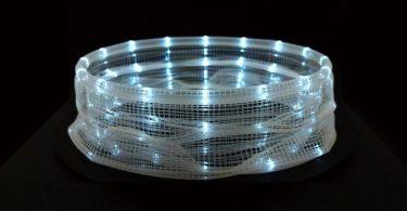 Оживший свет на гранях неправильной вращающейся цилиндрической формы создает движение танца
