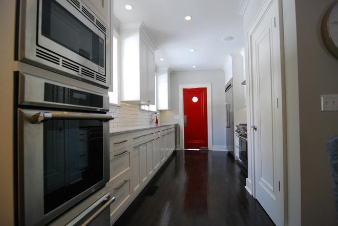 Яркая маятниковая дверь в интерьере белой кухни