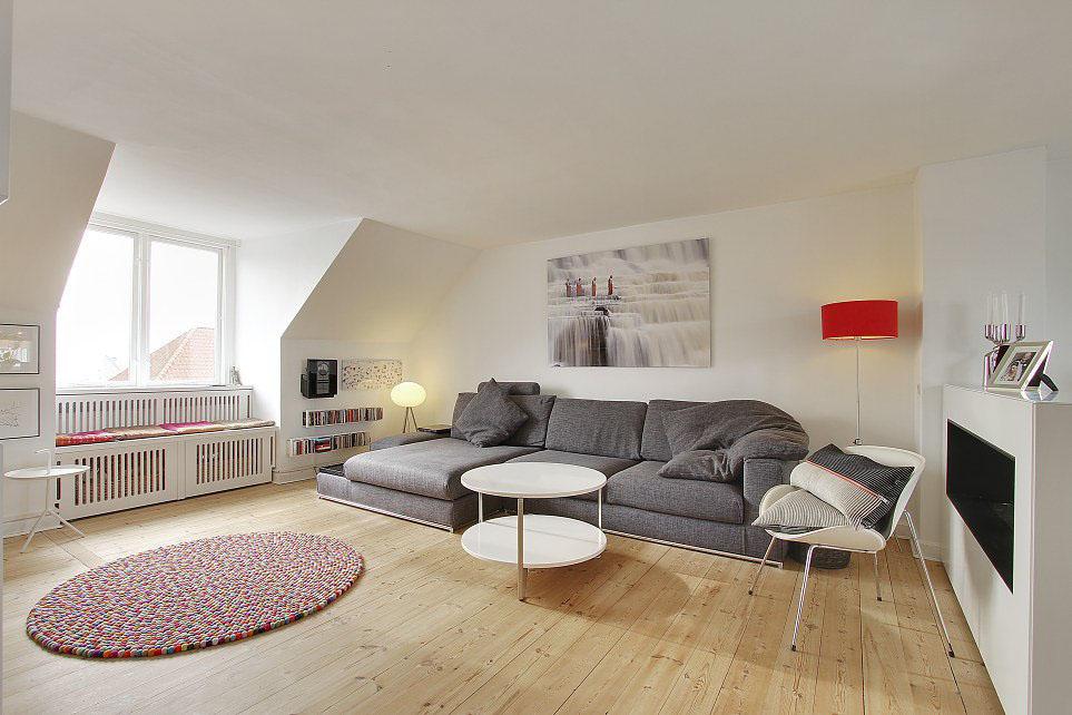 Угловой серый диван, столик, стулья и ковер в комнате выполненной в скандинавском стиле