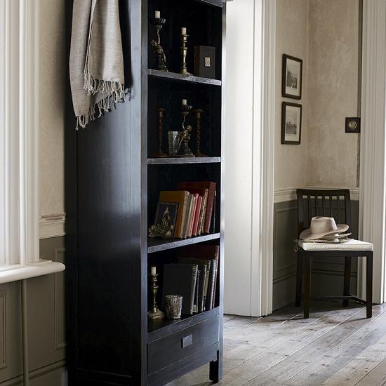 Тёмный книжный шкаф в интерьере гостиной