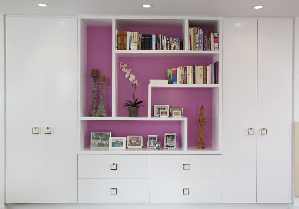 Стена за открытыми полками розового цвета