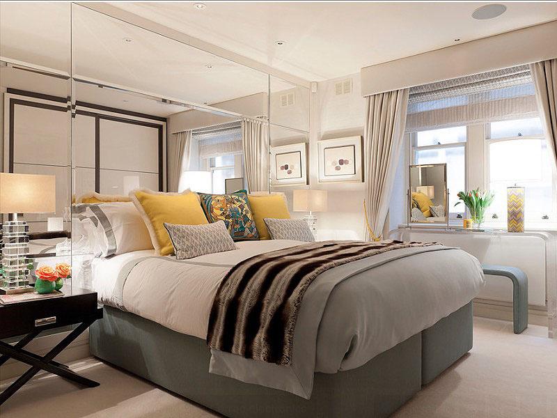 Зеркальная стена у изголовья кровати в интерьере спальни