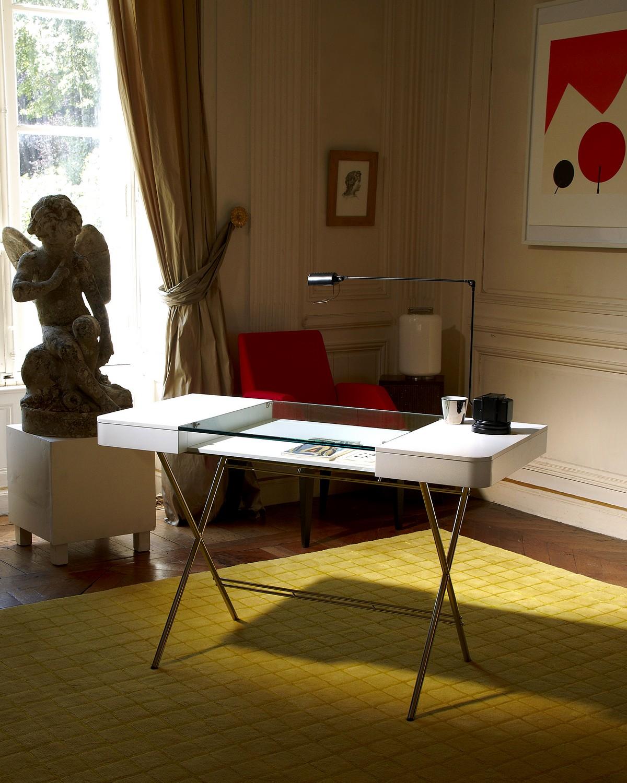 Стильный офисный стол со стеклянной столешницей в интерьере комнаты