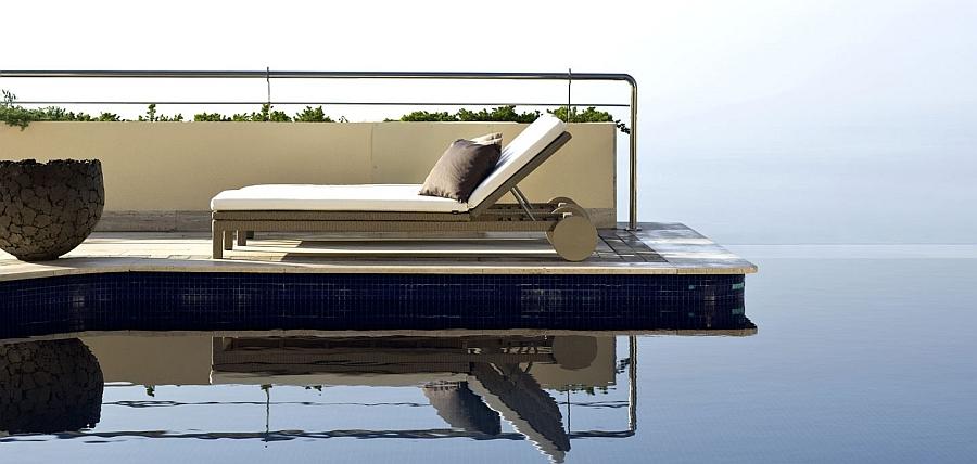 Шезлонг с подушками у бассейна