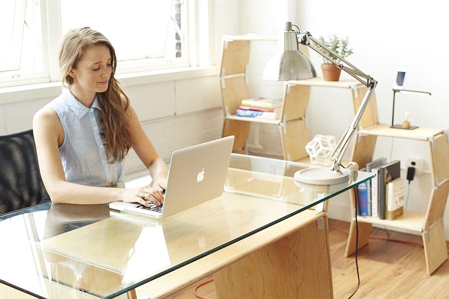 Стильный стол с стеклянной столешницей, светильник и ноутбуком на нем