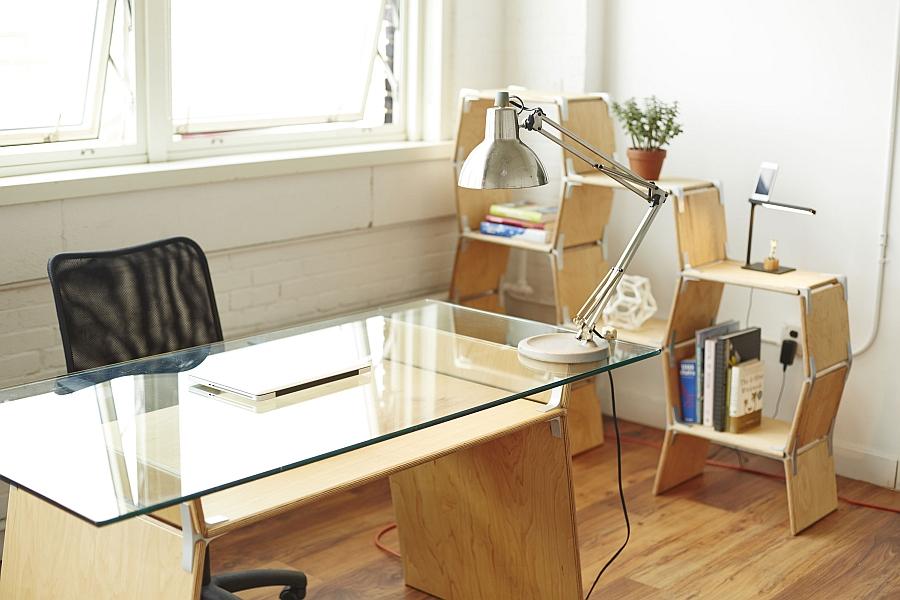 Офисный стол, светильник и модульный стеллаж у окна