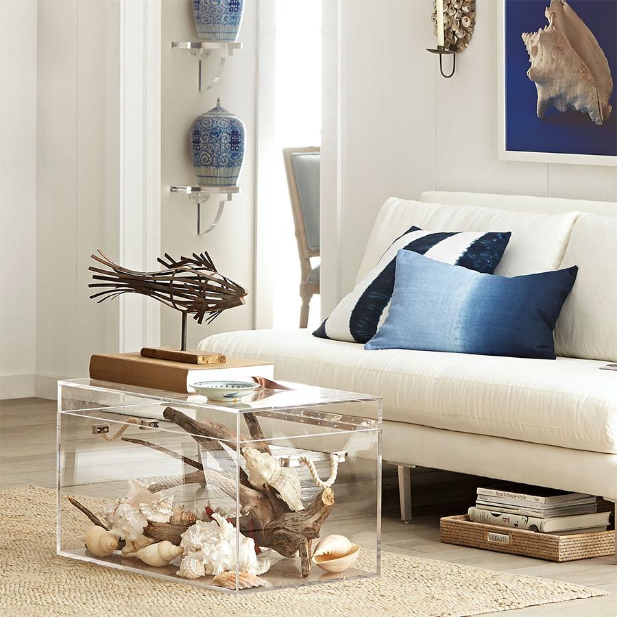 Акриловый прозрачный журнальный столик кубической формы в стильном интерьере гостиной